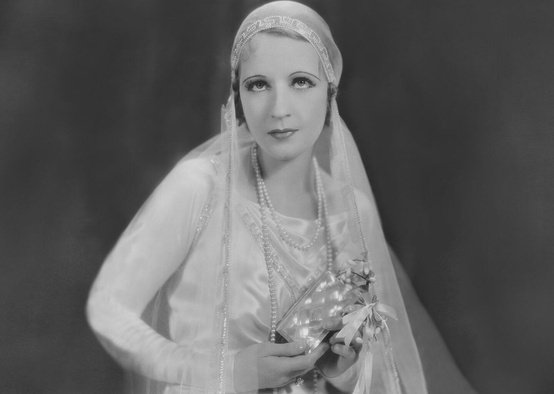 siyah beyaz fotoğrafta 1950'lerden nostaljik bir gelin elinde çiçek tutuyor