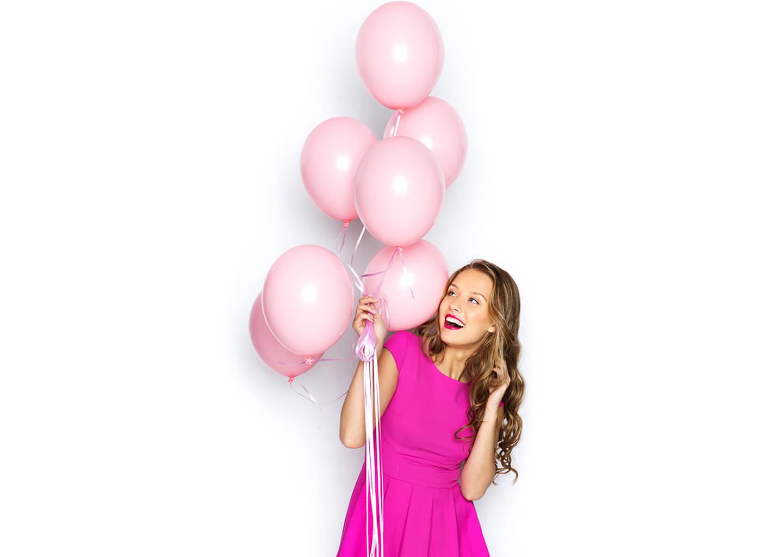 beyaz zemin üzerinde koyu pembe elbise giymiş genç bir kız elinde uçuk pembe balonlarla gülümseyerek poz veriyor