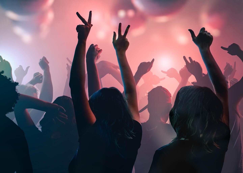 Gece kulübü gibi bir yerde sırtları dönük ellerini havaya kaldırarak dans eden insanlar