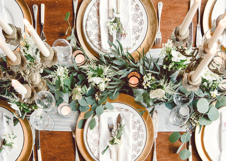 Yeşil yaprak ve krem rengi desenli tabaklardan oluşan masa
