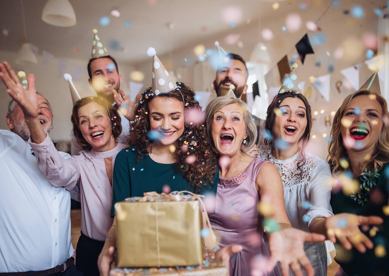 genç kadın ailesi ve arkadaşlarıyla doğum gününü kutluyor