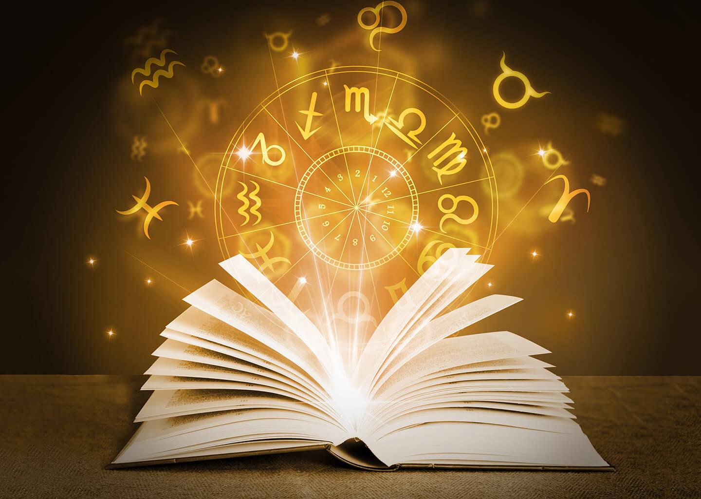 açık bir kitabın sayfaları arasından astroloji sembolleri parlıyor