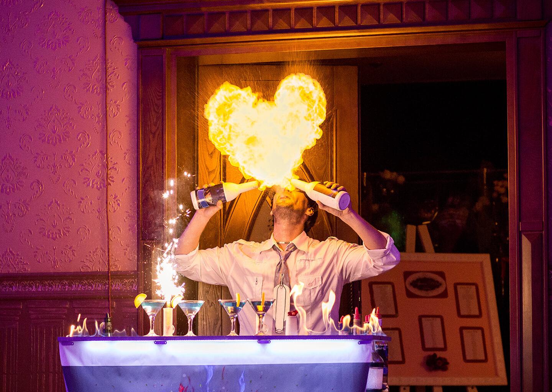 barmen alkol şişelerine ateş üfleyerek alevden kalp şekli oluşturuyor