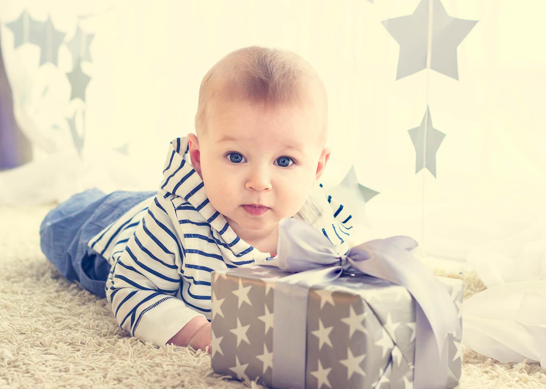erkek bebek ve önünde yıldızlı bir hediye paketi