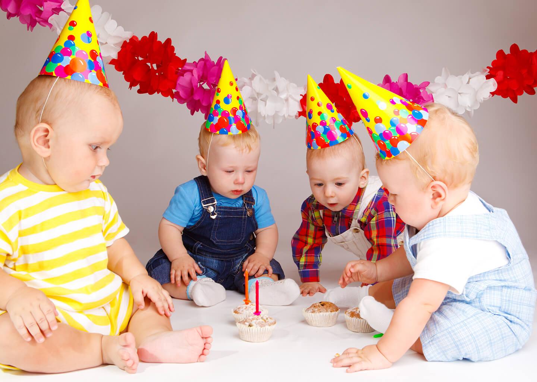 parti şapkası takmış bir grup bebek, üzerinde mum olan keklere bakıyor