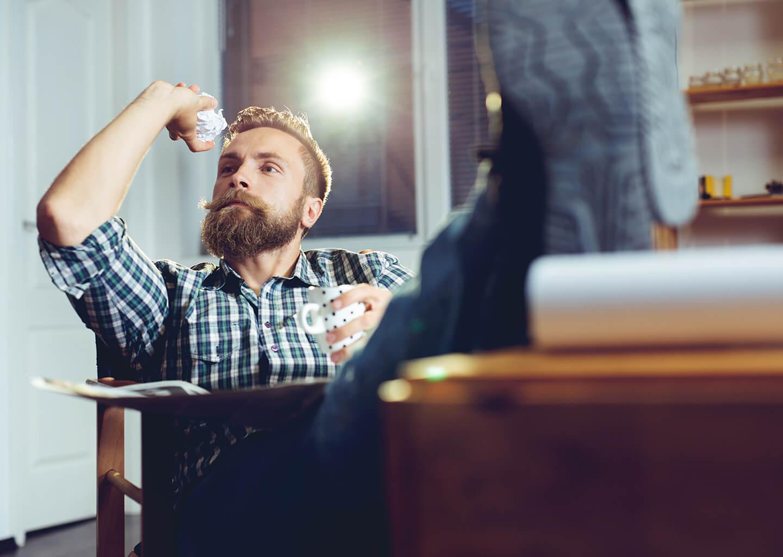 ayakalarını masaya uzatmış çöp kutusuna kağıt fırlatan sakallı adam