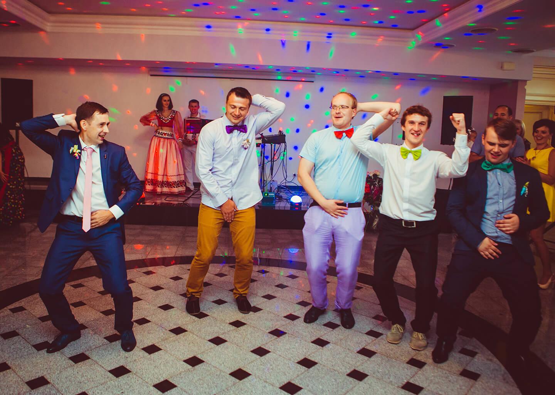 damat ve renkli pantolonlu arkadaşları düğün salonunda dans ediyor