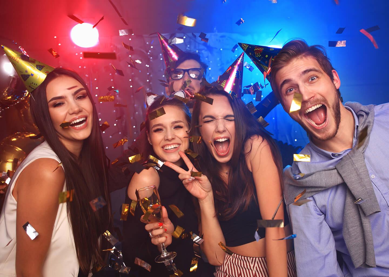 kafalarında parti şapkası olan gençler parti yapıyorlar