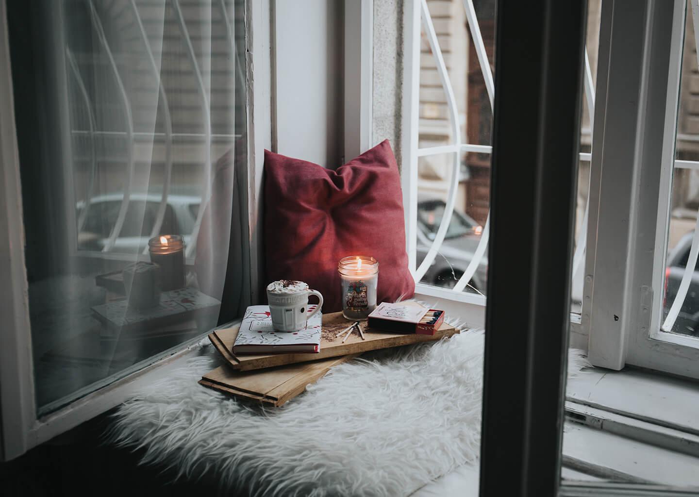 huzurlu bir pencere köşesinde mum kahve ve kitap