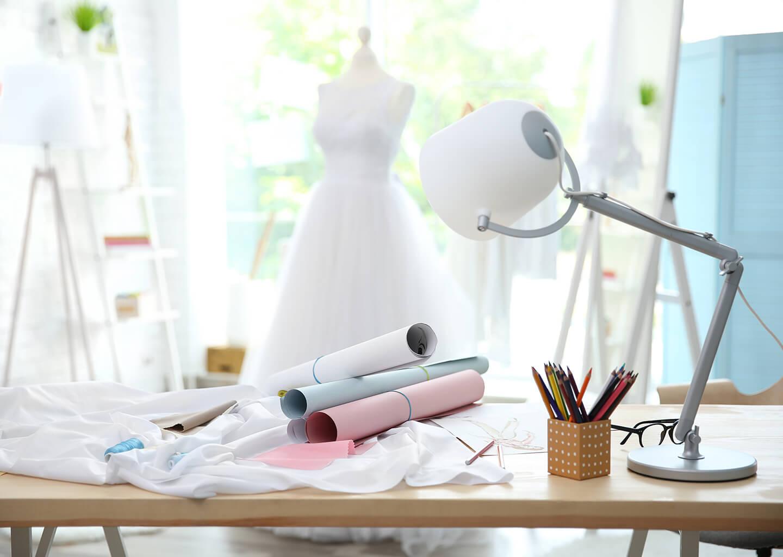gelinlik tasarımı için masanın üzerinde duran kumaşlar ve kağıtlar