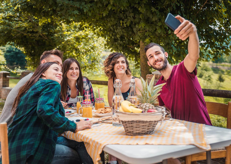 açık havada kahvaltı yapan gençler selfie çekiyor