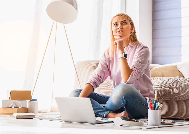 laptop karşısında yerde oturan ciddi bir karar almaya çalışan kadın
