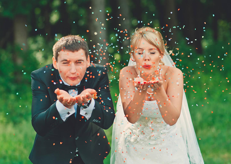 düğünde gelin ve damat açık alanda ellerindeki renkli konfetileri üflüyorlar