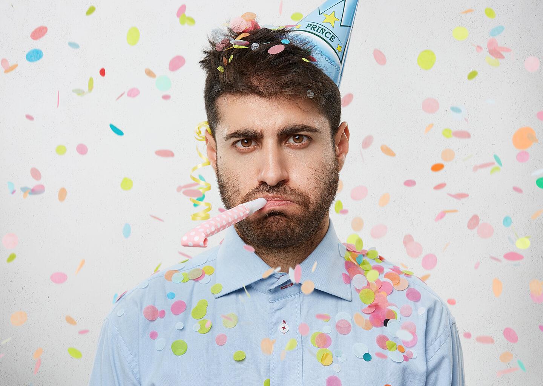 konfetiler yağarken kafasında doğum günü şapkası olan mutsuz adam