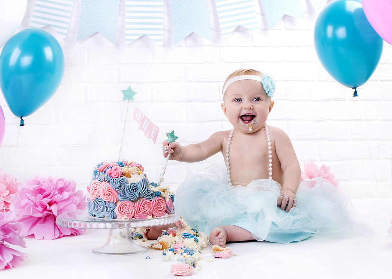 mavi etekli sevimli bebek, mavi balon ve süsler ile doğum günü pastası yiyor