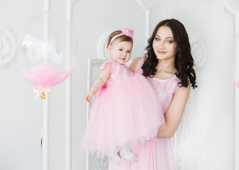 anne ve bebek pembe elbiseleriyle uyumlu takım giyinmişler