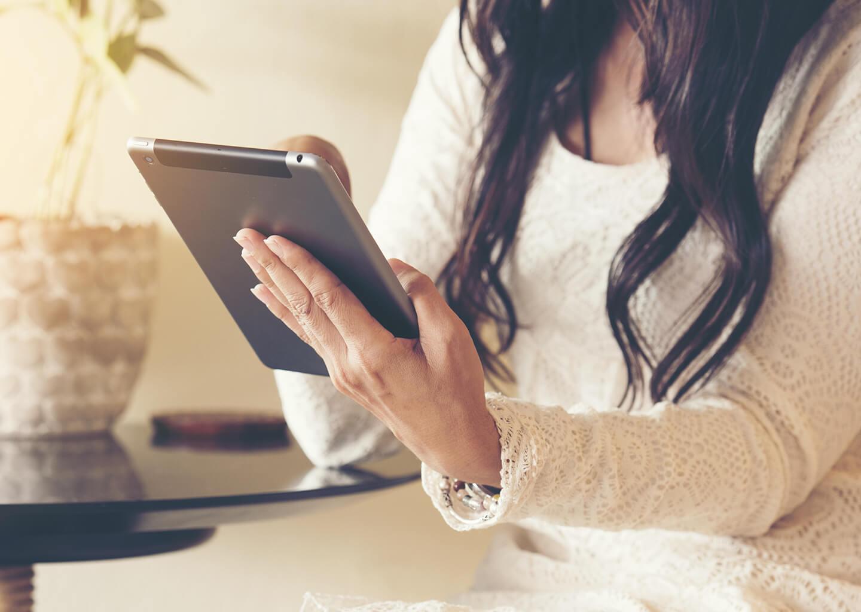 beyaz elbiseli kadın elindeki tablette işlem yapıyor