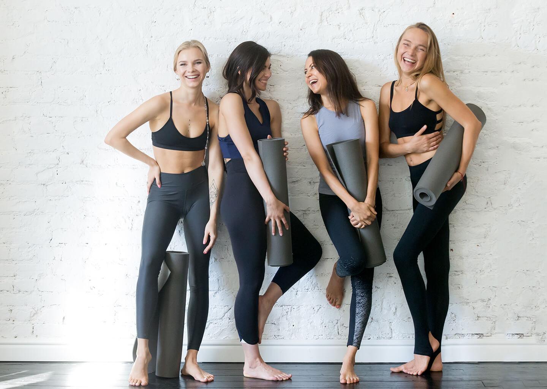 spor kıyafetleri olan neşeli kadınlar ayakta duruyor gülüşüyorlar