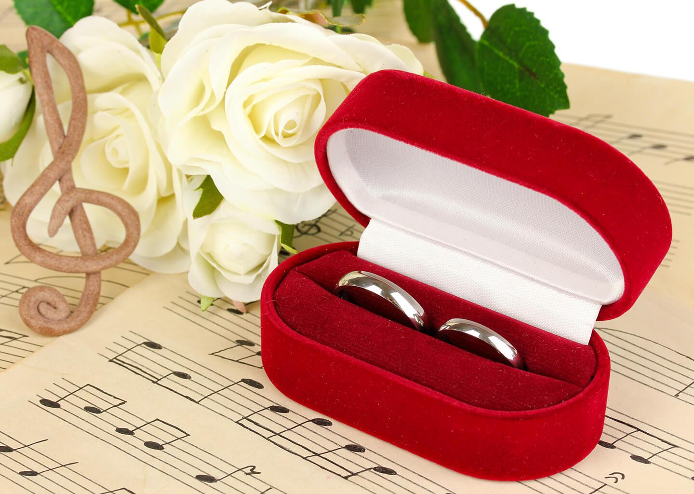müzik notaları yazılı kağıdın üzerindeki nikah yüzükleri